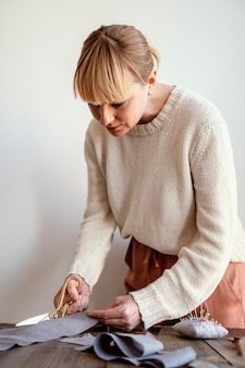 Вид сбоку женщина режет ткань