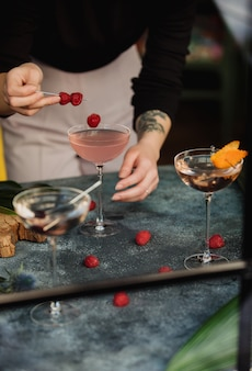 Side view of a woman decorating a pink cocktail with berries