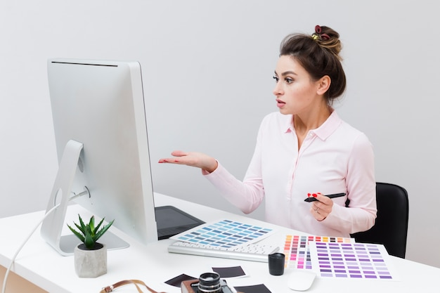 Side view of woman at desk looking at computer and not understanding what happened