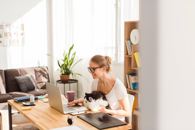 Side view of woman at desk with cat working from home