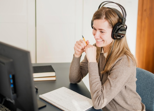 Side view of woman at desk with headphones participating in online class