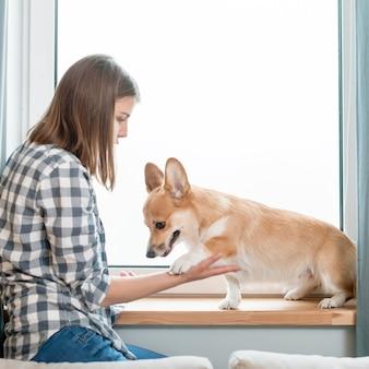 Vista laterale della donna e del cane davanti alla finestra