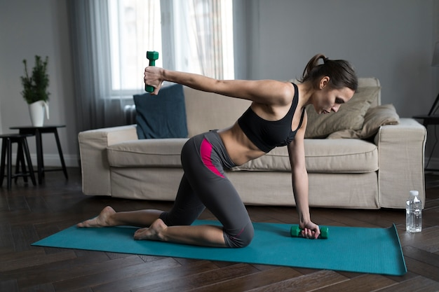 Side view of woman doing exercises with weights at home