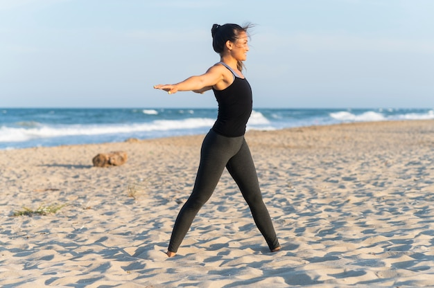 Side view of woman doing fitness on the beach