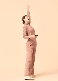 彼女の携帯電話からカラオケをしている側面図の女性