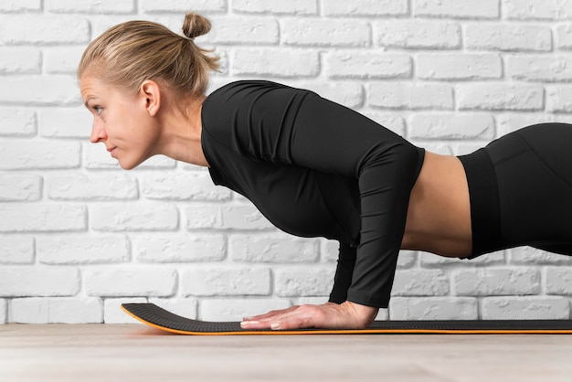 Side view woman doing plank