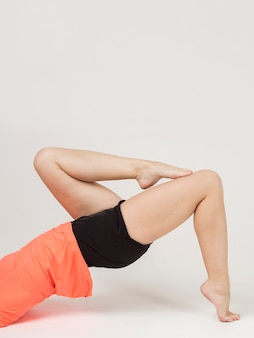 Side view of woman doing poses with her legs