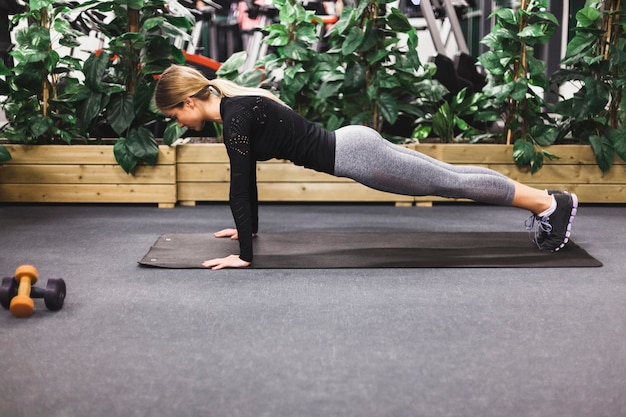 Side view of a woman doing push ups on exercise mat