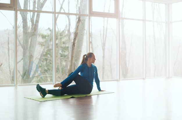 Side view of woman doing stretching in studio during morning time