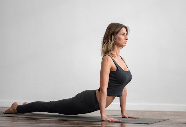 Vista laterale della donna che fa yoga a casa