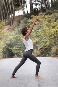 Vista laterale della donna che fa yoga in natura