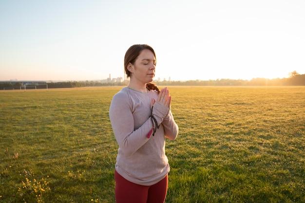 Vista laterale della donna che fa yoga all'aperto