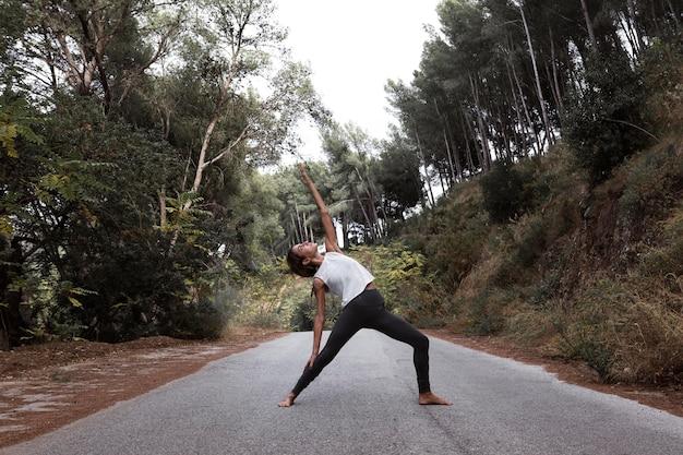Vista laterale della donna che fa yoga sulla strada in natura