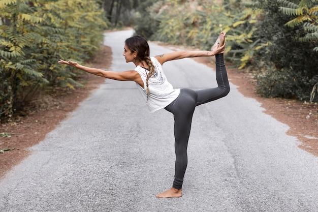 Vista laterale della donna che fa yoga sulla strada fuori