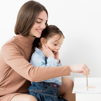 Side view of woman drawing with little girl