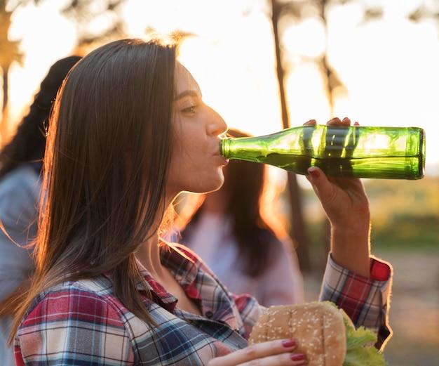 Vista laterale della donna che beve birra all'aperto con gli amici