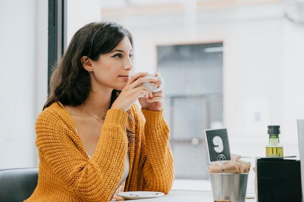 Donna di vista laterale che beve nel caffè