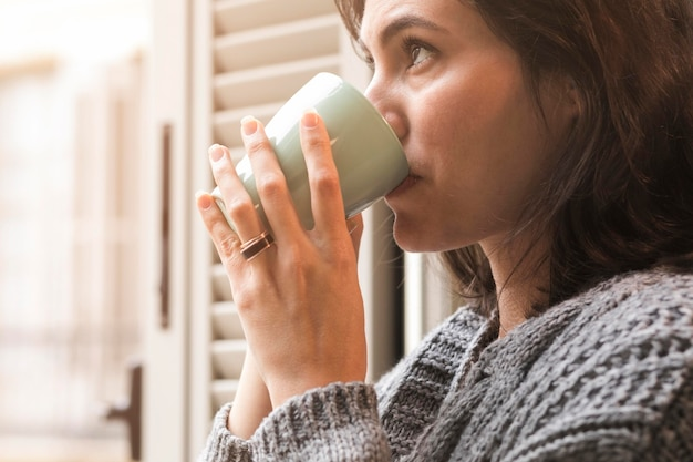 Side view woman drinking coffee