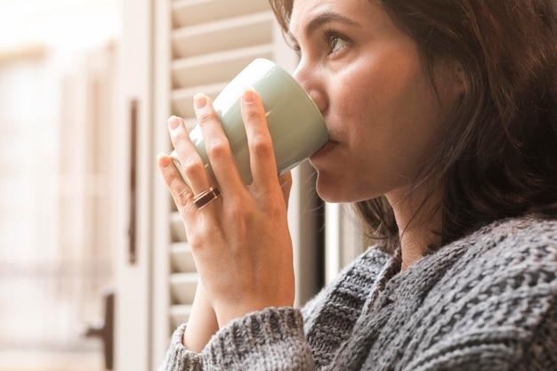 コーヒーを飲む側面図の女性