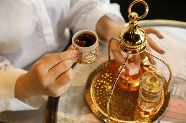 トルコの喜びと水のガラスとトルコのコーヒーを飲む女性の側面図
