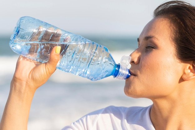Side view of woman drinking water on the beach after exercising