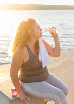 Side view of woman drinking water by the lake after working out