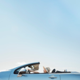 Side view of woman driving cabriolet