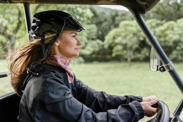 Donna di vista laterale che conduce automobile della jeep