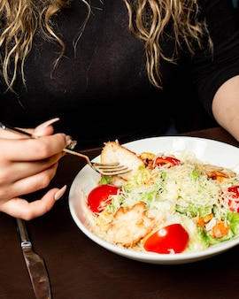 Side view of a woman eating caesar salad with chicken and parmesan cheese in bowl at the table