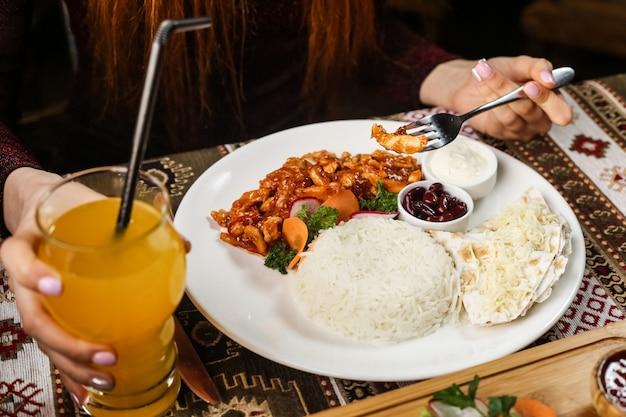 Вид сбоку женщина ест курицу в соусе с отварным рисом и соусами на тарелку с соком на столе