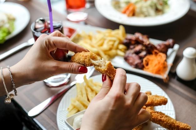 Вид сбоку женщина ест куриные наггетсы с картофелем фри и безалкогольный напиток