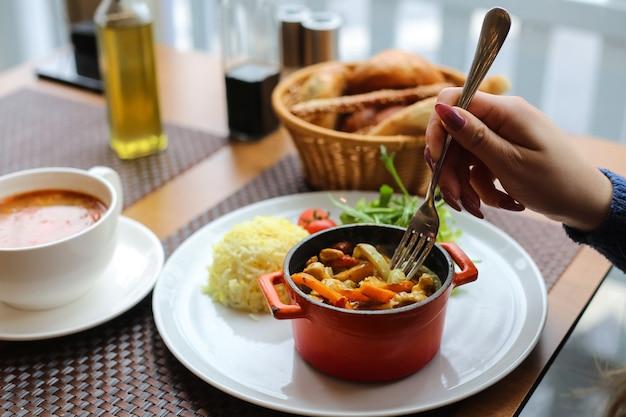Вид сбоку женщина ест курицу с овощами в кастрюле с рисом и зеленью с помидорами на тарелке
