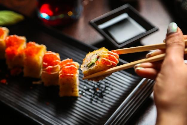 Вид сбоку женщина ест жареные суши в соусе с палочками и соевым соусом на подставке