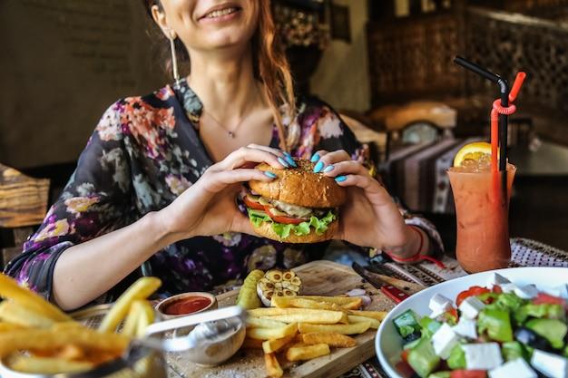 Вид сбоку женщина ест мясной бургер с картофелем фри кетчупом и майонезом на деревянной подставке