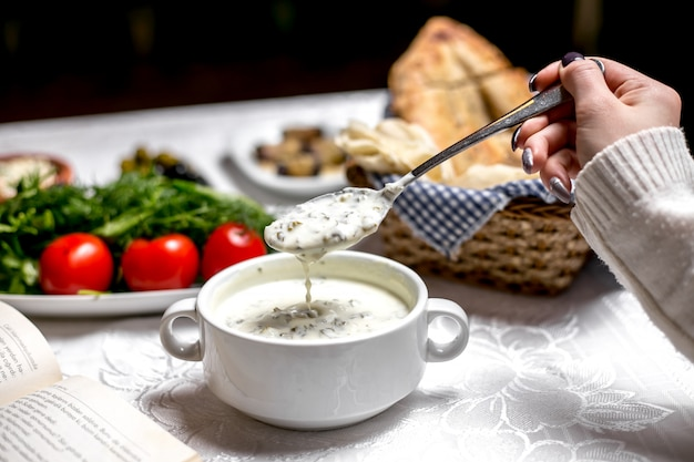 Side view a woman eating a traditional azerbaijani dish dovga-yogurt soup with vegetables and herbs