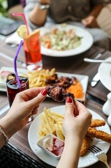 Side view woman eats barbecue wings with french fries and ketchup with mayonnaise on a plate