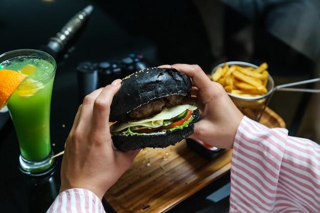 Вид сбоку женщина ест черный гамбургер с картофелем фри и кетчупом с майонезом на подставке с коктейлем
