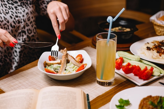La donna di vista laterale mangia l'insalata di caesar con il pollo e il pomodoro affettato con il cetriolo e il succo