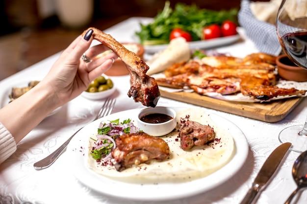 Vista laterale una donna mangia costolette di agnello kebab con salsa e cipolle