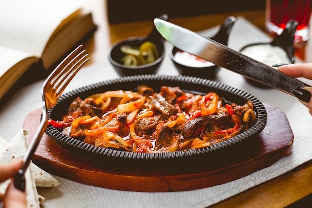 Side view a woman eats meat fajitos in a pan