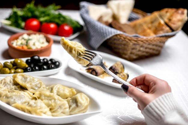 La donna di vista laterale mangia il gyurza azero tradizionale del piatto con le olive