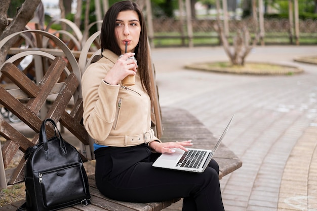 Side view of woman enjoying drink outdoors while working on laptop