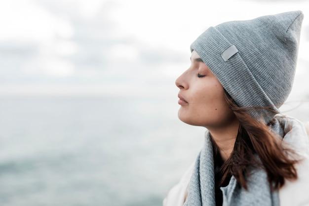 Vista laterale della donna che gode della brezza dell'oceano con lo spazio della copia