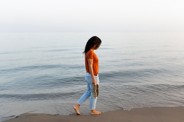 Side view of woman enjoying a walk by the beach