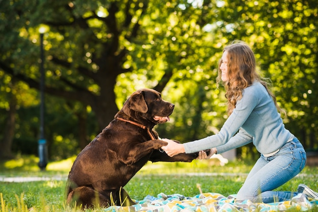 Side view of a woman enjoying with her dog in garden