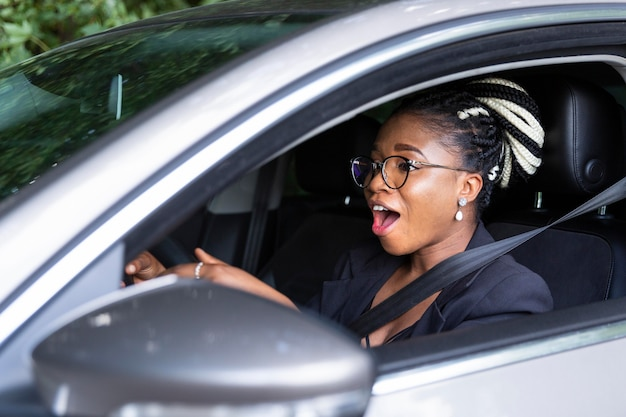 Side view of woman excited to drive her personal car