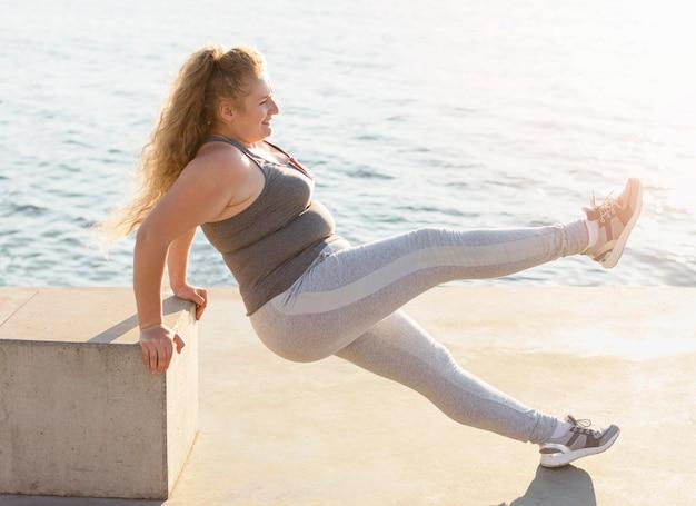 Vista laterale della donna che esercita in riva al lago