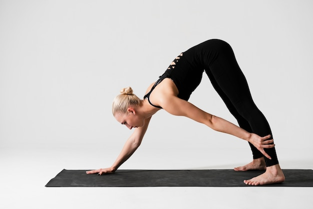Side view woman exercising on mat