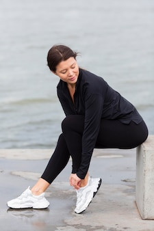 Side view of woman exercising outdoors in active wear