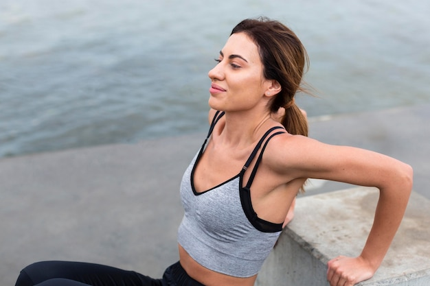 Side view of woman exercising outdoors by herself